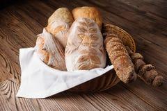 Diversas clases de pan y de baguettes en una cesta de mimbre en una tabla de madera Imagen de archivo libre de regalías