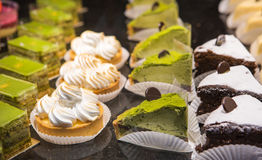 Diversas clases de postre dulce se apelmazan con las bayas y el te verde Fotos de archivo