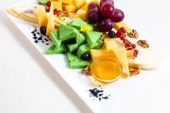 Diversas clases de queso, uvas cortadas, rojas, nueces, miel en un cuenco, pasa roja, queso verde, soporte de madera Imágenes de archivo libres de regalías