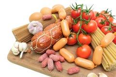 Diversas comidas en una tabla de cortar en un fondo blanco Imagen de archivo libre de regalías