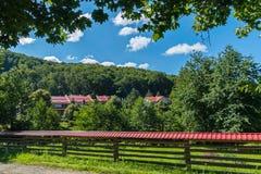 Diversas construções com os telhados vermelhos cercados com uma cerca e umas plataformas de madeira com um telhado e as telhas de Foto de Stock Royalty Free