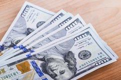 Diversas contas de cem-dólar na tabela Imagem de Stock Royalty Free