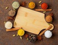 Diversas especias indias en tazas del metal El tablero de madera vacío, top compite foto de archivo