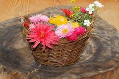 Diversas flores del jardín de las flores y calabazas ornamentales en una cesta Fotografía de archivo
