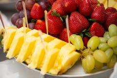 Diversas frutas adornadas en la placa en el restaurante, casandose el abastecimiento Piña, fresa, uva verde Foto de archivo