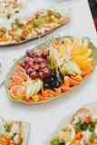 Diversas frutas cortaron en porciones en una placa, un pomelo, una naranja, uvas y una pera entre otros platos En el partido imágenes de archivo libres de regalías