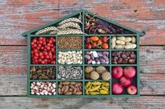 Diversas frutas sanas, semillas e ingrediente alimentario secado en caja de madera Imagenes de archivo