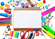 Diversas fuentes de escuela aisladas en el fondo blanco Cuaderno en el centro del concepto del marco de nuevo a escuela Foto de archivo libre de regalías