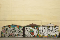 Diversas garagens com grafittis perto da parede amarela Imagens de Stock