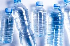 Diversas garrafas de água plásticas no fundo branco fotos de stock