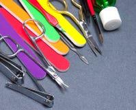 Diversas herramientas de la manicura en fondo texturizado gris Fotografía de archivo libre de regalías