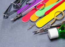 Diversas herramientas de la manicura en fondo texturizado gris Fotografía de archivo