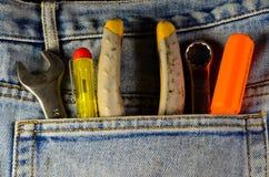 Diversas herramientas de la mano en un bolsillo de los vaqueros fotos de archivo libres de regalías