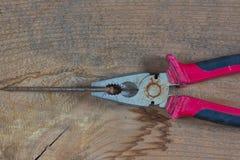 Diversas herramientas en un fondo de madera Clavos, alicates imagenes de archivo