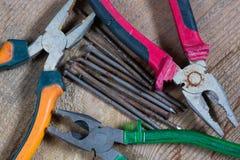 Diversas herramientas en un fondo de madera Clavos, alicates foto de archivo