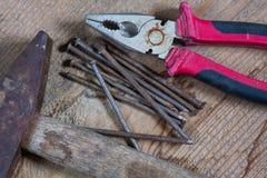 Diversas herramientas en un fondo de madera Clavos, martillo, alicates Imágenes de archivo libres de regalías