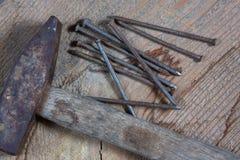 Diversas herramientas en un fondo de madera Clavos y un martillo foto de archivo
