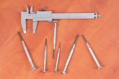 Diversas herramientas en un fondo de madera - destornillador, calibrador de la construcción Foto de archivo libre de regalías