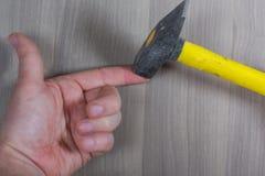 Diversas herramientas en un fondo de madera El martillo pegó un finger del ` s foto de archivo