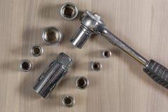 Diversas herramientas en un fondo de madera Llave plegable con las cabezas permutables Imagen de archivo libre de regalías