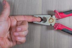 Diversas herramientas en un fondo de madera Los alicates pellizcan sus fingeres fotografía de archivo