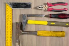 Diversas herramientas en un fondo de madera Martillo, cincel, alicates, cuadrado Fotos de archivo