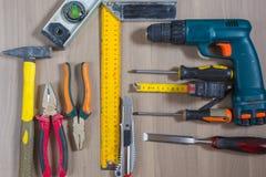 Diversas herramientas en un fondo de madera Martillo, taladro, alicates Destornillador, regla, cortando los alicates Foto de archivo