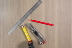 Diversas herramientas en un fondo de madera Regla, lápiz, cuchillo, ruleta fotos de archivo libres de regalías