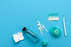 Diversas herramientas para el cuidado dental en fondo azul Cepillo de dientes, despedregadora, seda, flossers, cera para los apoy imagen de archivo
