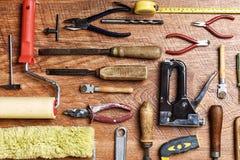 Diversas herramientas para la reparación: alicates, taladros, rodillos, martillo en un fondo de madera Imágenes de archivo libres de regalías