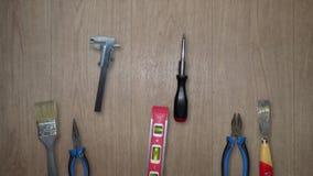 Diversas herramientas que mueven encendido el fondo de madera almacen de metraje de vídeo