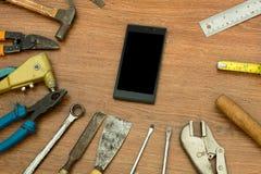 Diversas herramientas viejas con el teléfono elegante en la madera Fotos de archivo libres de regalías