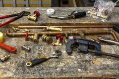 Diversas herramientas y colocaciones de la fontanería en un banco de trabajo Imágenes de archivo libres de regalías