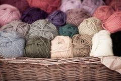 Diversas lanas coloridas roscan bolas en cesta de mimbre Imagen de archivo libre de regalías