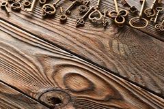 Diversas llaves del metal en fondo de madera foto de archivo