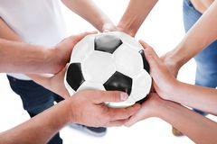 Diversas mãos que mantêm unida a esfera de futebol Fotografia de Stock Royalty Free
