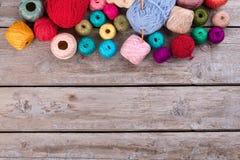 Diversas madejas multicoloras en fondo de madera retro Fotografía de archivo libre de regalías