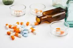 Diversas medicaciones y píldoras con las botellas de la farmacia del vintage en un fondo blanco fotos de archivo