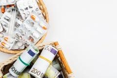 Diversas medicaciones y píldoras con los billetes de banco euro en un fondo blanco fotografía de archivo