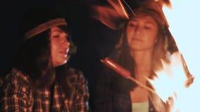 Diversas meninas sentam-se pelo fogo na noite e fritam-se salsichas Discuta e conduza a conversação Vieram em uma campanha video estoque