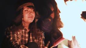 Diversas meninas sentam-se pelo fogo na noite e fritam-se salsichas Discuta e conduza a conversação Vieram em uma campanha filme