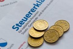 Diversas moedas douradas no formulário suíço da declaração de imposto, Zurique foto de stock