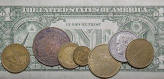 Diversas monedas en billete de banco de 1 dólar Foto de archivo