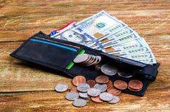 Diversas monedas en la cartera, la bandera americana y los billetes de banco ciento Imagen de archivo libre de regalías