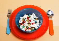 Diversas píldoras particolored en una placa Fotografía de archivo libre de regalías