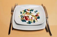 Diversas píldoras particolored en una placa Imagen de archivo libre de regalías