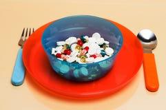 Diversas píldoras particolored en una placa Fotos de archivo