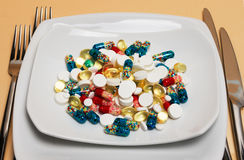 Diversas píldoras particolored en una placa Fotografía de archivo