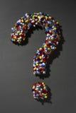 Diversas píldoras que forman el signo de interrogación en fondo negro Imagen de archivo libre de regalías