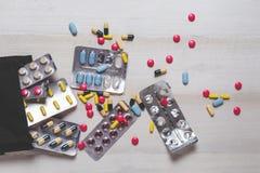 Diversas píldoras, tabletas y cápsulas coloridas en la tabla de madera blanca, visión superior Imágenes de archivo libres de regalías
